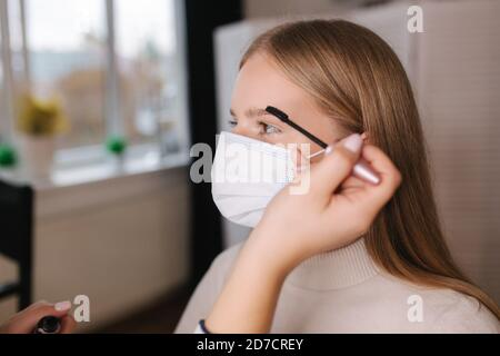 Female makeup artist working in beauty salon during quarantine. Make up artist in medical mask. Beautiful blond hair model in protective mask Stock Photo