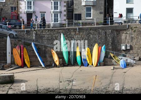 Canoes and kayaks leant up against the harbour wall in Mousehole Cornwall, UK - Stock Photo