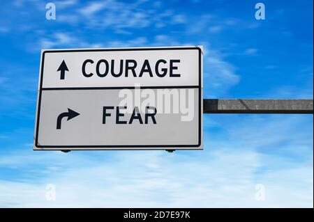 Courage versus fear. White two street signs with arrow on metal pole. Directional road. Crossroads Road Sign, Two Arrow. Blue sky background. - Stock Photo