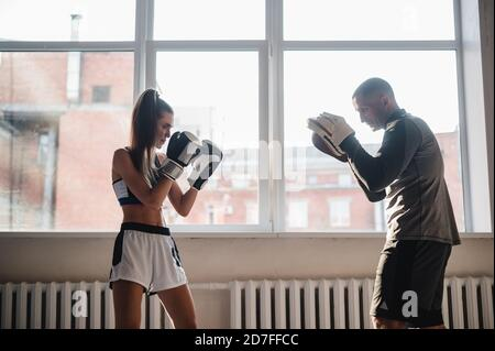 A man with boxing paws on his hands teaches the technique of hitting a novice girl in a light gym - Stock Photo