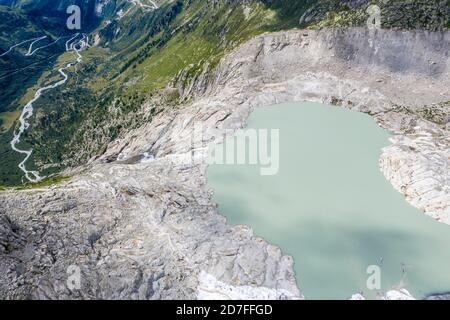 Drone shot of melting Rhone glacier, glacial lake, source of Rhone river, Switzerland. - Stock Photo