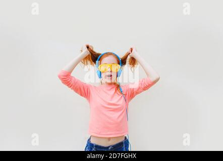 a teenage girl with red hair wearing yellow glasses and blue headphones is dancing near a white wall