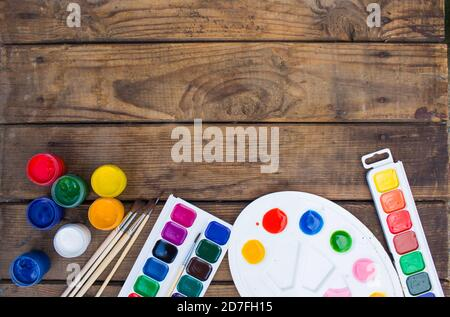 multi-colored paints,brushes palette, brush,lie on a wooden background top view