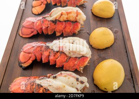 Lobster tails that are saddleback style cooked with lemons - Stock Photo