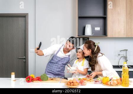 Young Asian family are preparing salad in the kitchen and father take a photo selfie by phone. Excited smiling and felling happy. parent teach daughte - Stock Photo