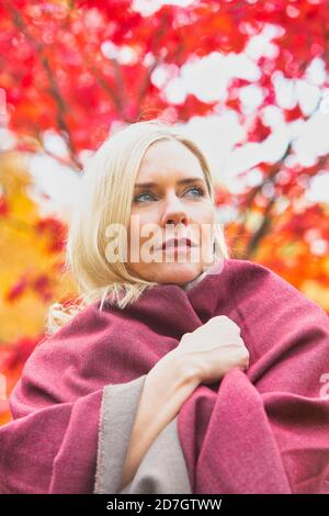 portrait of blond woman in her 40s outdoors in autumn