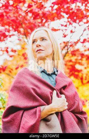 portrait of blond woman in her 40s outdoors in autumn looking thoughtful