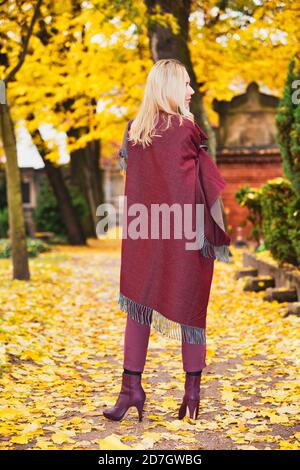 backside of blond woman standing outdoors in a park in autumn