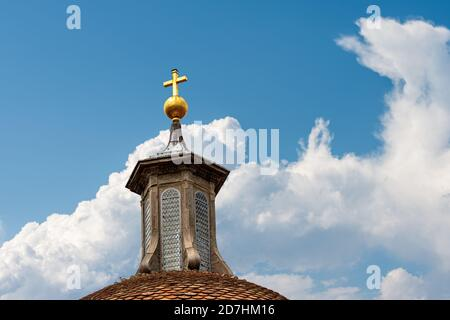 Basilica di Santo Spirito (1444-1487) in Florence downtown, Tuscany, Italy, Europe. Detail of the dome with lantern and golden cross on blue sky.