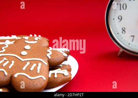 Beautiful vintage silver alarm clock and in the foreground plate of gingerbread cookies on a bright red background. Time concept. Holiday routine. Wai