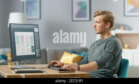 Handsome Focused Young Man Works on a UX UI Mobile App Template, Uses Personal Computer while Sitting at His Desk in the Cozy Apartment.