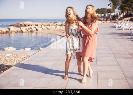 Female friends walking on sidewalk against sea during sunny day