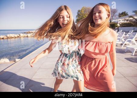 Friends laughing while walking on sidewalk against sea
