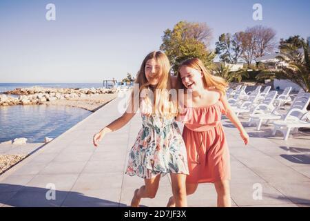 Friends enjoying while walking on sidewalk against sea
