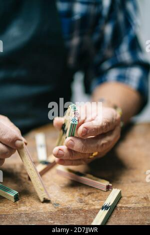 Luthier holding wood stick while working at workshop