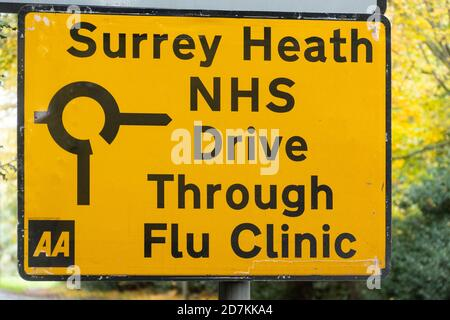 Road sign to an NHS drive through flu clinic providing influenza jabs vaccinations immunizations, Surrey, UK - Stock Photo