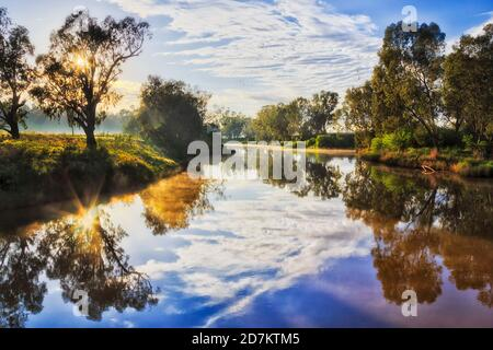 Reflection of the sun in calm still waters of Macquarie river at sunrise in Dubbo city of Australia.