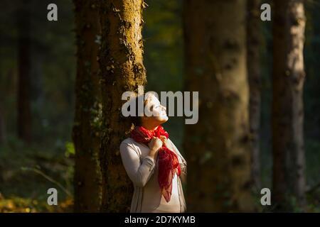 Shorthaired short hair haired teengirl as countrygirl enjoy enjoying patch of sunlight sun peering peer through woodland trees looking away upwards up - Stock Photo