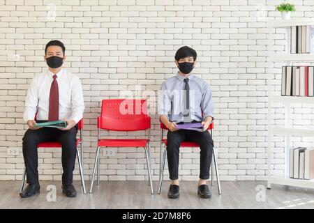 Two Asian men sit in red plastic chairs spaced out with Matt to cover their mouths to prevent COVID-19 waiting for a job interview.
