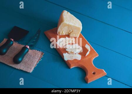 Composed cloesup detail view of aged cheddar cheese with cheese knife set, over vintage blue wooden backdrop - Stock Photo