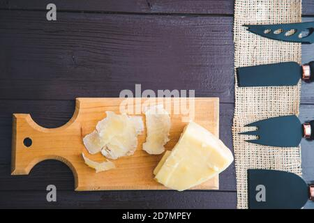 Composed Flat lay detail view of aged cheddar cheese with cheese knife set, over vintage brown wooden backdrop with copy space - Stock Photo
