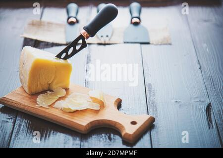 Composed cloesup detail view of aged cheddar cheese with cheese knife set, over vintage brown wooden backdrop - Stock Photo