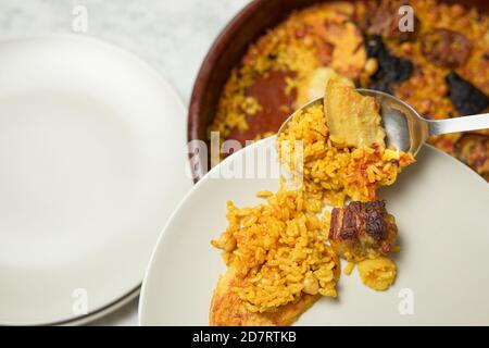 Man's hands serving oven-baked rice on a plate with a spoon. Valencia, Spain - Stock Photo