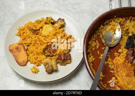 Plate with oven baked rice next to an earthenware casserole. Valencia, Spain - Stock Photo