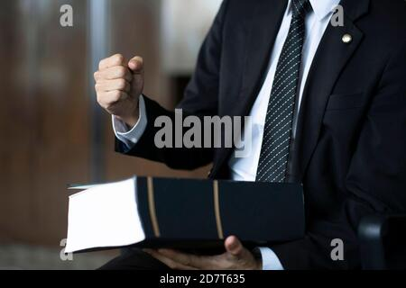 Lawyer holding fist with law book
