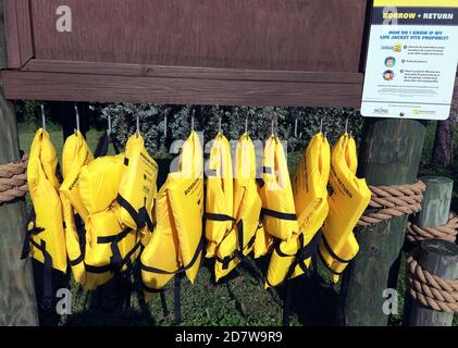 A row of bright yellow life jackets awaits boaters who have forgotten to bring a personal flotation device that helps ensure their safety at sea in the Gulf of Mexico along the west coast of Florida, USA. The buoyant vests are offered free of charge as part of a Borrow and Return program by the Sea Tow Foundation and the West Coast Inland Navigation District (WCIND). Loaner life preservers are available to prevent drownings in many places in the United States and other countries where recreation on the water is popular. - Stock Photo
