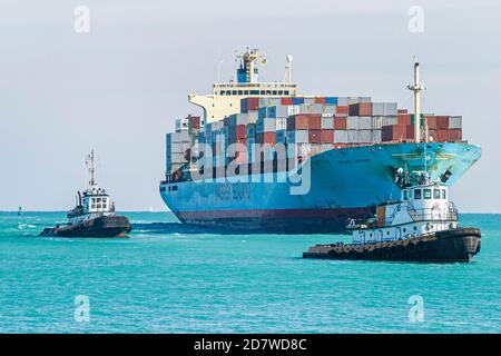 Florida Miami Beach Atlantic Ocean cargo container ship loaded, approaches approaching arrives arriving Port of Miami tugboats, - Stock Photo