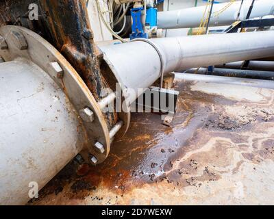 Leak from sewage water pipe. Thick bio waste leak from broken chrome iron piping. Breakthrough sewerage system. Water flows down the road from the sew - Stock Photo