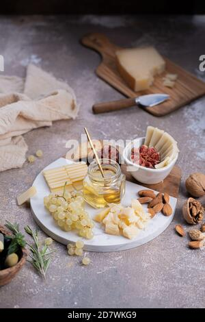 Assorted cheeses on marble board with figs, nuts, grapes and honey - Stock Photo
