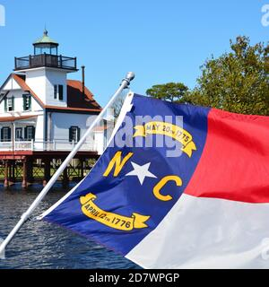 The North Carolina flag flying in front of a lighthouse. - Stock Photo
