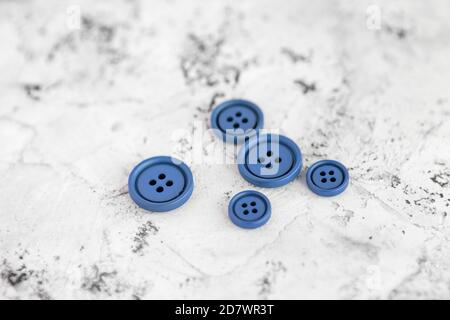 Pile of blue matte buttons on concrete background, macro bokeh. beautiful needlework. Use for sew. Space for text - Stock Photo