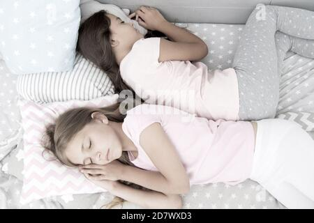reliable rear. healthy baby sleep. best friends. sisters in bed. sweet dreams. little girls pajama in bedroom. childhood happiness. kids friendship. sleeping small girls. family values. back to back.