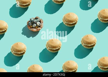 Colorful french cookies macarons pattern on pastel blue background. Minimal concept. Chocolate dessert, macaroon on colored surface. Daylight, natural