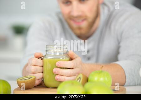 healthy man drinking a green juice detox smoothy Stock Photo