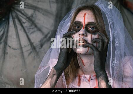 Horror, nightmare and Halloween concept. Dead bride. Young woman in dead man's bloody make-up with bridal veil on her head looks into camera, touching - Stock Photo