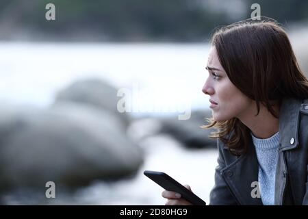 Sad woman looking away holding smart phone alone on the beach
