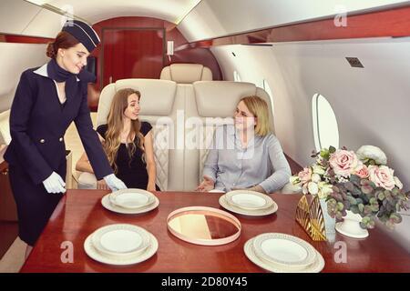 Air hostess inside airplane serves first class passengers.