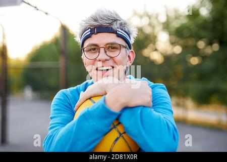 young caucasian teen boy playing basketball, handsome guy in casual sportswear alone at basketball playground, practice