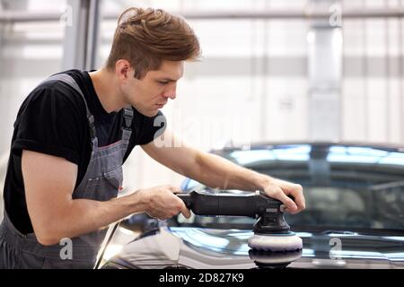 car detailing and polishing concept. young professional car service male worker, auto mechanic with orbital polisher,automobile concept