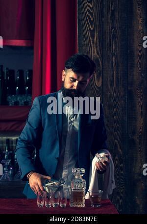 Barman pouring brandy in whiskey glass. Waiter bartender in bar. - Stock Photo