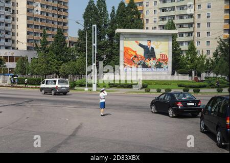 08.08.2012, Pyongyang, North Korea, Asia - Everyday street scene depicts a saluting traffic girl in the middle of an intersection with passing traffic. - Stock Photo