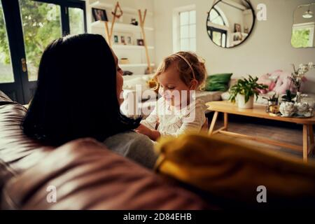Happy young mother sitting on the couch smiling and playing with her child in the living room