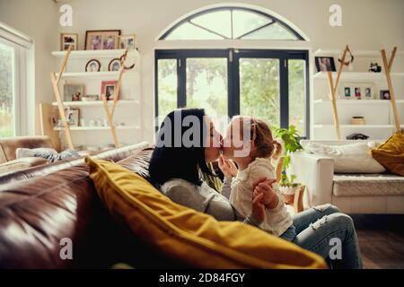 Playful young woman kissing toddler girl while sitting on sofa at home
