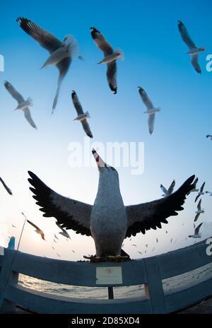 Bird statue as birds fly over BangPu Thailand - Stock Photo