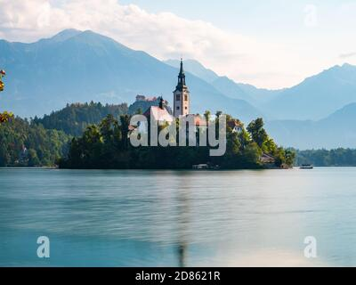 Long exposure of Lake Bled Slovenia, early morning, cloudy day, reflections in the water, side view of the island and mountains in the foreground - Stock Photo