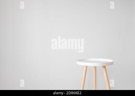 Empty white coffee table in front of grey wall. Scandinavian style, minimalism in house, tranquil living, backdrop and copy space for advertising and